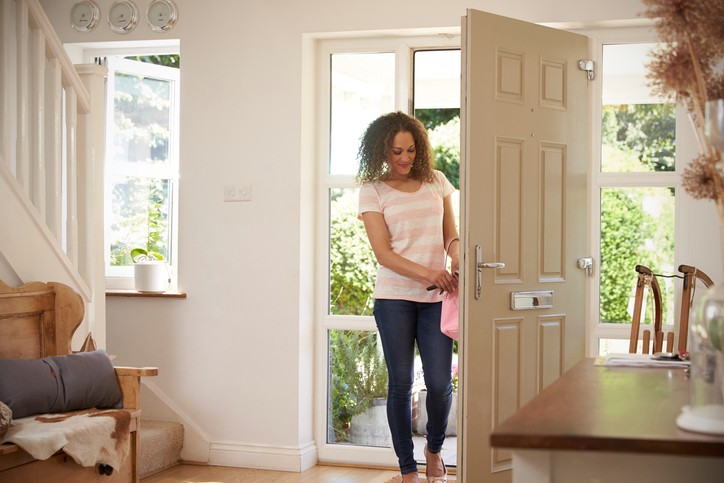 Woman Returning Home And Opening Front Door